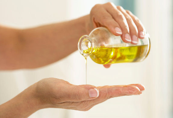 Woman pouring oil from bottle onto palm